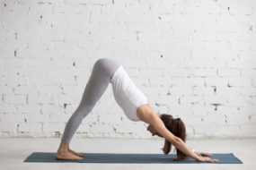 Beautiful young woman working out indoors, doing yoga exercise in the room with white walls, downward facing dog pose, adho mukha svanasana (surya namaskar posture), full length, copy space